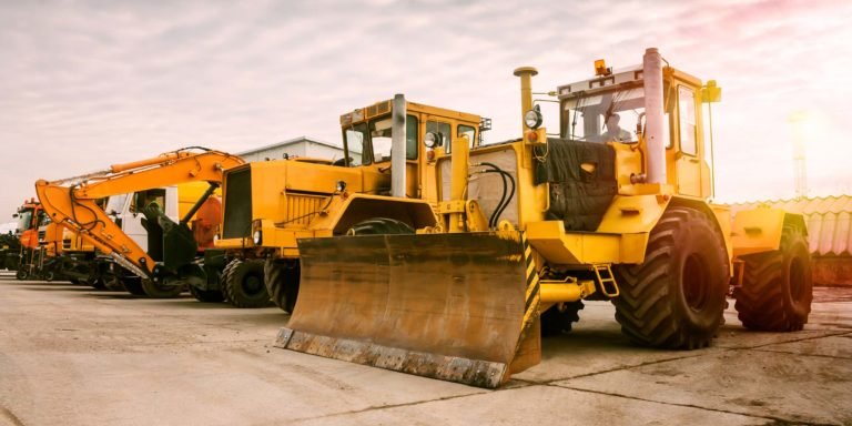 A row of wheel loaders at bay in a construction yard.