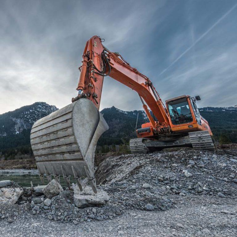 Excavator at work on rock pile