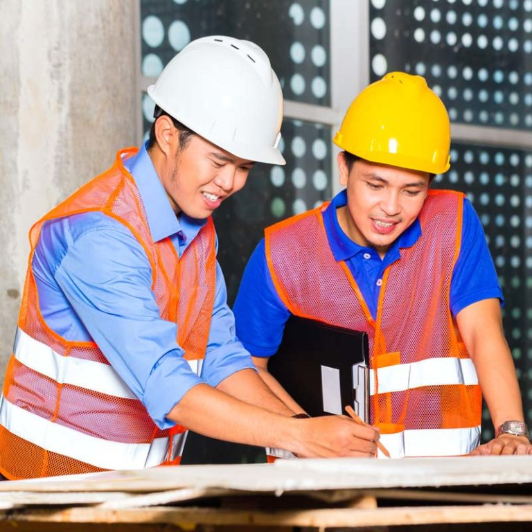 Two construction foremen reviewing plans